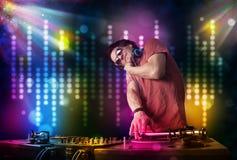 Il DJ che gioca le canzoni in una discoteca con lo spettacolo di luci Fotografia Stock Libera da Diritti