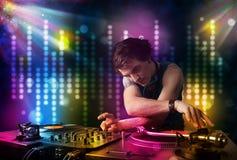 Il DJ che gioca le canzoni in una discoteca con lo spettacolo di luci Immagini Stock Libere da Diritti