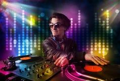 Il DJ che gioca le canzoni in una discoteca con lo spettacolo di luci Fotografie Stock