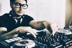 Il DJ che gioca musica al primo piano ed alle miscele del miscelatore la pista nel night-club fotografie stock