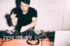 Il DJ che gioca musica al primo piano ed alle miscele del miscelatore la pista nel night-club fotografie stock libere da diritti
