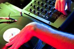 Il DJ che graffia i record nell'ambiente del randello Fotografia Stock