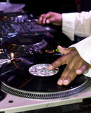 Il DJ che graffia sulle piattaforme girevoli Immagini Stock