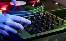 Il DJ che per mezzo di entrambe le mani su un'impostazione del miscelatore Fotografia Stock Libera da Diritti