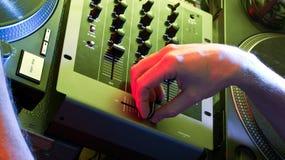 Il DJ che utilizza una mescolanza in un ambiente del randello Fotografie Stock