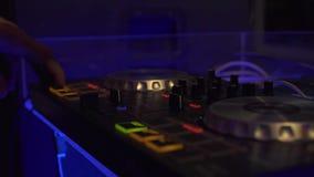 Il DJ consola per musica da ballo mescolantesi e luce variopinta nel club della discoteca Giocatore del miscelatore del DJ e cons archivi video