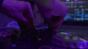 Il DJ controlla la console di musica e la luce variopinta in night-club Giocatore del miscelatore del DJ e console del suono per  stock footage