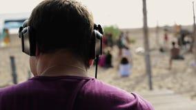 Il DJ in cuffie alla piattaforma girevole sulla spiaggia Sorriso in macchina fotografica Giorno pieno di sole di estate stock footage
