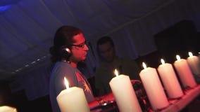 Il DJ in cuffie che filano alla piattaforma girevole sul partito in night-club Riflettori rossi intrattenimento Candele stock footage