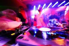 Il DJ dietro le piattaforme in un night-club Fotografie Stock Libere da Diritti