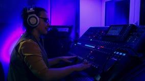 Il DJ femminile alle piste mescolantesi mescolantesi della console alla discoteca video d archivio