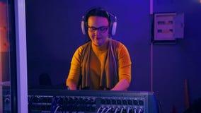 Il DJ femminile con le cuffie in una stanza tecnica conduce una discoteca ad una console mescolantesi alla luce di una discoteca archivi video