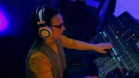 Il DJ femminile in cuffie che mescolano le piste per la discoteca su una console mescolantesi video d archivio