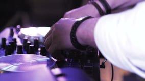 Il DJ gioca la miscelazione e lo scratch di musica sull'attrezzatura di musica della piattaforma girevole Attrezzatura profession video d archivio
