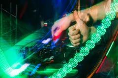 Il DJ gioca la musica sul miscelatore in un night-club con fondo vago Immagine Stock