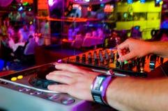 Il DJ mescola la pista nel locale notturno ad un partito Fotografia Stock Libera da Diritti
