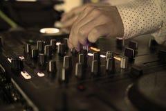 Il DJ mescola la pista in night-club al partito con la gente di dancing sul fondo della sfuocatura Fotografia Stock