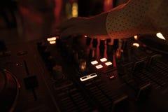 Il DJ mescola la pista in night-club al partito con la gente di dancing sul fondo della sfuocatura Immagine Stock
