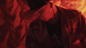 Il DJ nello snapback e cuffie che giocano musica sulla piattaforma girevole alle luci rosse vicino su archivi video