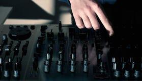 Il DJ passa la miscelazione sul miscelatore dell'audio bordo Fotografia Stock