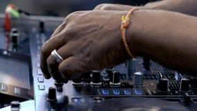 Il DJ sta mescolando le piste di musica sull'audio console stock footage