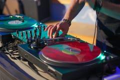Il DJ sulle annotazioni di vinile dietro la console Fotografie Stock