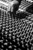 Il DJ usa un pannello del miscelatore fotografia stock