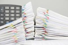 Il documento ed il calcolatore di sovraccarico del mucchio hanno lavoro di ufficio della sfuocatura come priorità alta Fotografia Stock