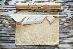 Il documento sgualcito rotoli di carta d'annata plume sul bordo di legno fotografia stock libera da diritti