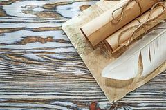 Il documento sgualcito rotoli di carta medievali plume sul bordo di legno fotografia stock
