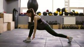 Il doiung castana femminile atletico bello giovane dà una stoccata l'allenamento alla palestra Preparandosi per l'estate Forma fi video d archivio