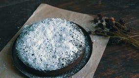 Il dolce al forno casalingo del brownie del cioccolato in polvere con lo zucchero a velo si trova di recente accanto ai fiori sec video d archivio