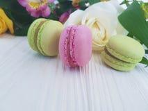 Il dolce dolce colorato del macaron tradizionale è aumentato su un fondo di legno bianco, francese di alstroemeria Fotografie Stock Libere da Diritti