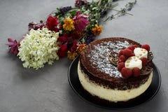 Il dolce coperto di cioccolato ha decorato i lamponi, con un mazzo dei fiori su un fondo grigio Immagini Stock Libere da Diritti