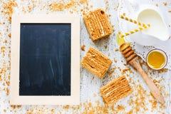 Il dolce di miele collega il latte e le briciole del miele sulla tavola di legno bianca a Fotografie Stock