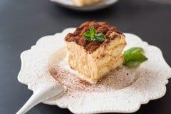 il dolce di tiramisù del dessert ha decorato la menta su fondo nero Fotografia Stock