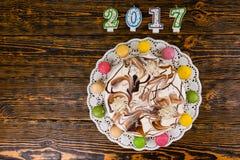 Il dolce e i macarons del nuovo anno si avvicinano alle candele il numero 2017 sulle sedere di legno Fotografia Stock