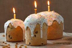 Il dolce ucraino tradizionale di pasqua della cultura ha chiamato il kulich pane dolce con tre candele brucianti e glassa sul tes Immagini Stock