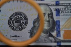 Il dollaro aumenta tramite una lente d'ingrandimento, controllo per falsità Fotografie Stock Libere da Diritti