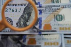 Il dollaro aumenta tramite una lente d'ingrandimento, controllo per falsità Fotografia Stock Libera da Diritti
