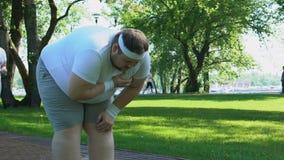 Il dolore acuto ritenente dell'uomo obeso in petto durante pareggiare, signora lo aiuta, problemi stock footage