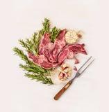Il doppio lombo crudo dell'agnello taglia con l'erba e le spezie della forcella della carne su fondo di legno bianco Fotografie Stock