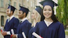 Il dottorando asiatico con il diploma, sorridente nella macchina fotografica, internazionale studia archivi video