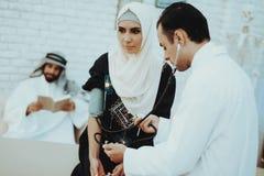 Il dottore arabo Checking Heartbeat una donna musulmana fotografia stock libera da diritti
