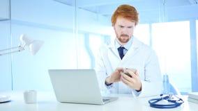 Il dottore Browsing Online sul telefono in ospedale, testarossa immagini stock