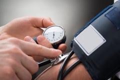 Il dottore Checking Blood Pressure di un paziente Fotografie Stock Libere da Diritti
