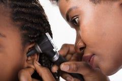 Il dottore Checking Girl Ear in ospedale fotografie stock libere da diritti