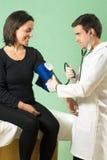 Il dottore Checking Patients Blood Pressione-horiz Fotografia Stock Libera da Diritti