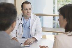 Il dottore In Conversation With una coppia allo scrittorio Immagini Stock