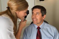 Il dottore di occhio che esamina paziente ispano Fotografie Stock Libere da Diritti